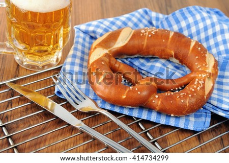 Pretzel on bavarian tablecloth. Beer glass aside with silverware on table - stock photo