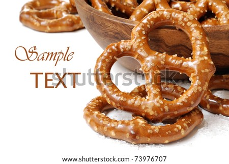 Pretzels with wooden bowl on white background with copy space.  Macro with shallow dof. - stock photo