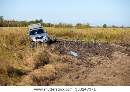 PRIAMURSKY, RUSSIA - OCTOBER 5, 2014: Mitsubishi Pajero Sport with rooftop tent stuck in deep mud