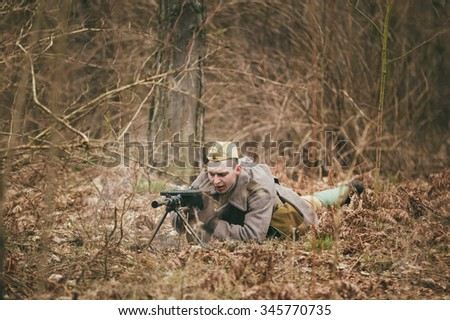 PRIBOR, BELARUS - April, 05, 2015: Unidentified re-enactor dressed as Soviet russian soldier olled on ground with a machine gun