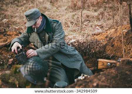 PRIBOR, BELARUS - April, 04, 2015: Unidentified re-enactors dressed as German Wehrmacht soldier in a trench settling for night