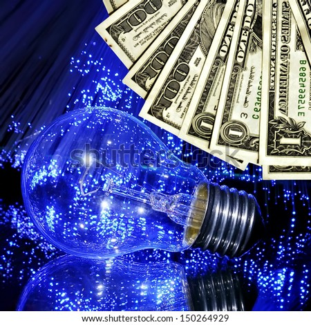Price increase on electricity. Electric bulb in light rays of fiber optics and banknotes (Dollars) - stock photo
