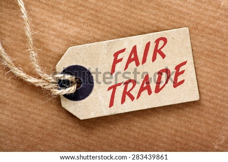 Price label or luggage tag with the phrase Fair Trade in red text with string and brown wrapping paper - stock photo