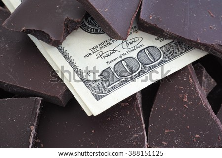 Price of chocolate. One hundred dollars and piece of chocolate. Chocolate prices concept. Close up.
