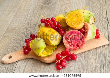 prickly pears and raspberries on cutting board - stock photo
