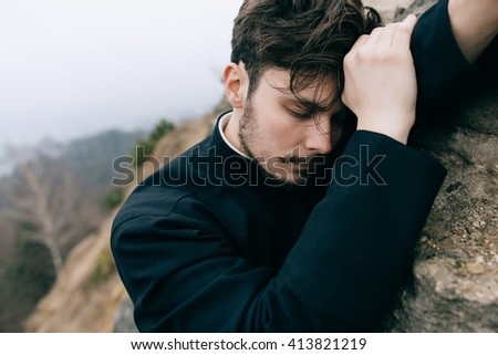 Priest bearded man thinks the stress in the mountains. Repentance - stock photo