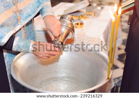 priest filling metal bowl with water - stock photo