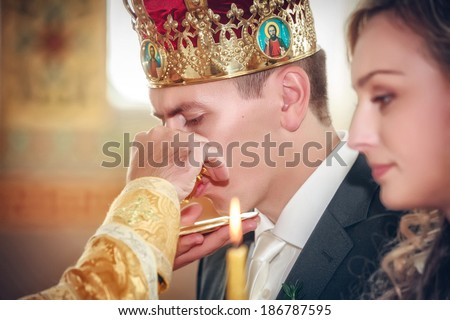 priest gives wine to a crowned groom during orthodox wedding ceremony  - stock photo