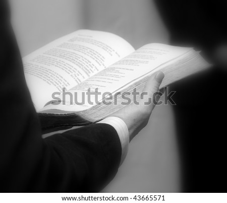 Priest holding a bible. Close up in black and white - stock photo