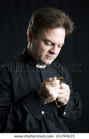 Priest holding his rosary and praying.  Black background and dramatic lighting. - stock photo