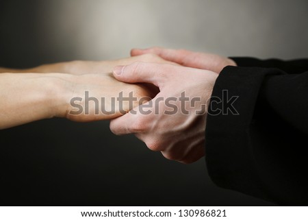 Priest holding woman hands, on black background - stock photo