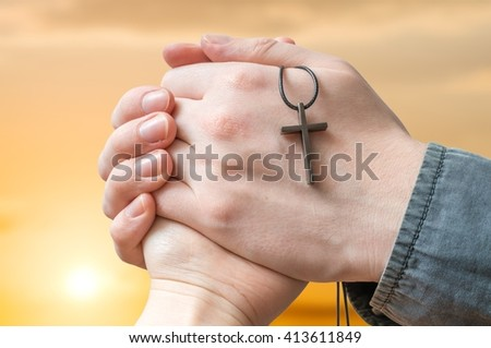 Priest is blessing woman at sun set. Clasped hands holding cross. - stock photo