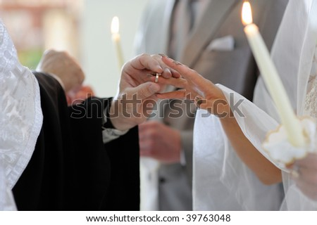 Priest is putting the ring on bride's finger during orthodox wedding ceremony - stock photo