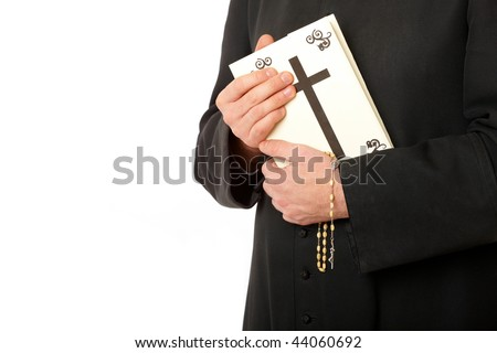 Priest's hands on bible with rosary. Real cassock. - stock photo