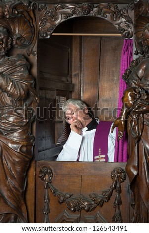 Priest sitting in 17th century confession booth listening to the repentant - stock photo