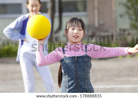 Primary Japanese girl playing dodge ball - stock photo