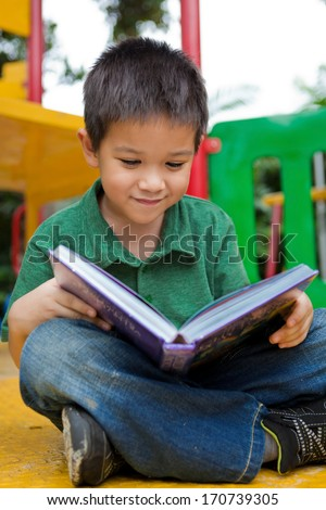 Primary school aged boy smiles as he reads his book outdoors in a playground. He is seated with his legs folded. Full body shot.