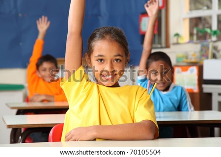 Primary school children signal with raised hands - stock photo