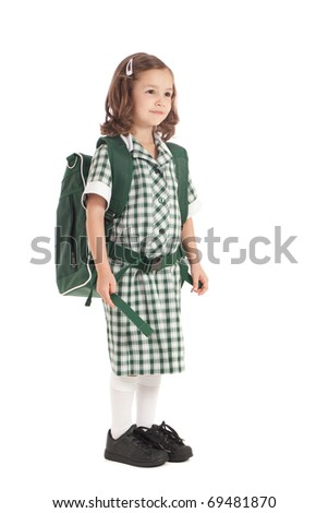 Primary school girl in uniform wearing backpack. Isolated on white.