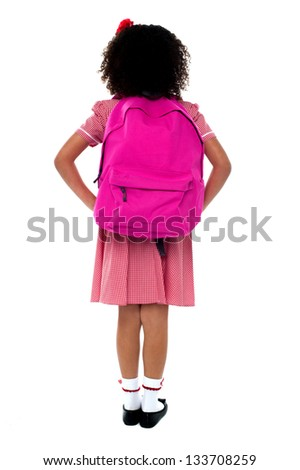 Primary school girl in uniform with school bag over shoulder. Isolated on white. - stock photo