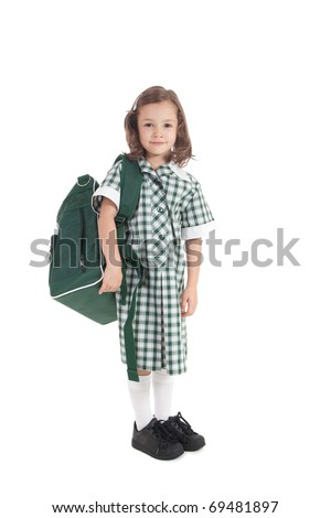 Primary school girl in uniform with school bag over shoulder. Isolated on white.