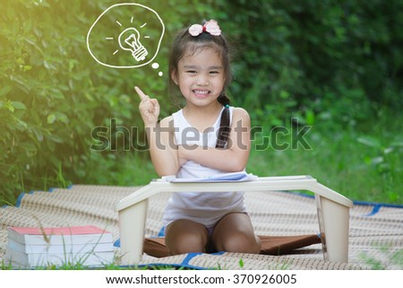 Primary school kid thinking about answer sitting at his desk - stock photo