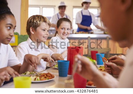 Primary school kids at a table in school cafeteria, close up