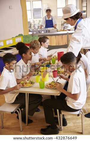 Primary school kids eat lunch in school cafeteria, vertical - stock photo