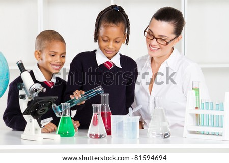 primary school students and teacher in science class - stock photo