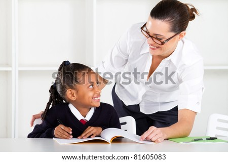 primary school teacher and pupil in classroom - stock photo