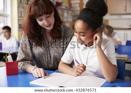 Primary school teacher with a schoolgirl in class, close up - stock photo