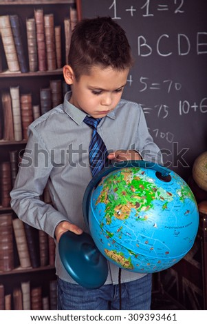 Primary schoolboy attentively studying globe - stock photo