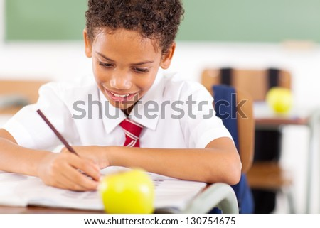 primary schoolboy busy writing class work - stock photo