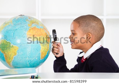 primary schoolboy using magnifying glass looking at globe - stock photo