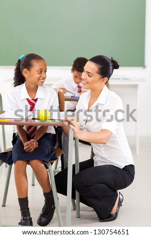 primary schoolgirl and teacher communicating during a lesson - stock photo