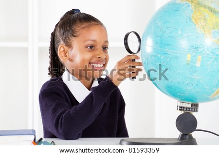 primary schoolgirl looking at globe using a magnifying glass - stock photo