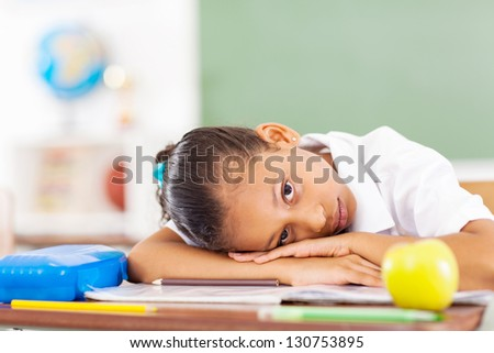 primary schoolgirl resting on desk