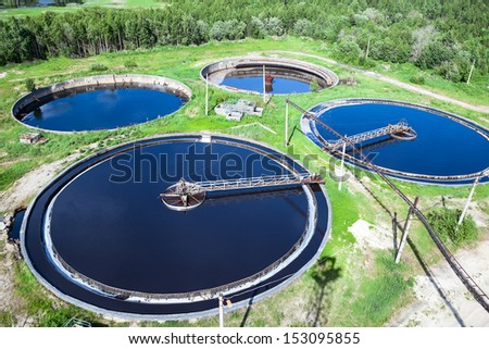 Primary sedimentation stage, sewage flowing through large circular tanks with mechanically driven scrapers - stock photo