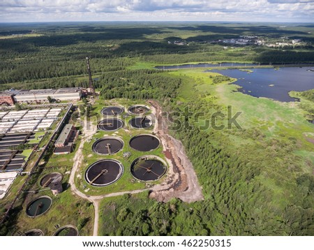 Primary settling tanks and clarifiers are on wastewater treatment plant in evergreen forest. Aerial view