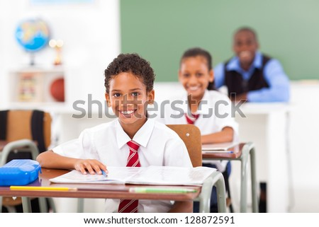 primary students and teacher sitting in classroom - stock photo
