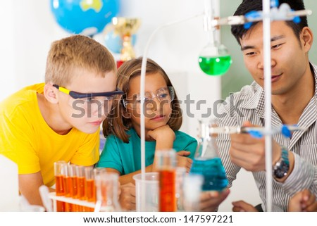primary students in science class with teacher - stock photo
