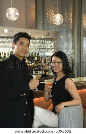 Prime adult Asian male and female at bar with cocktails.