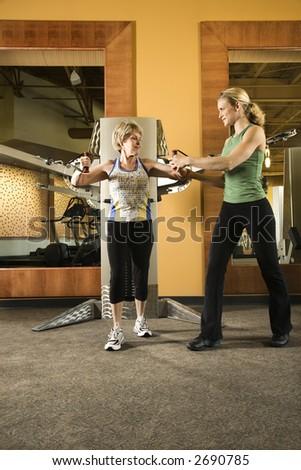Prime adult Caucasian female helping mature adult Caucasian female use exercise equipment at gym. - stock photo