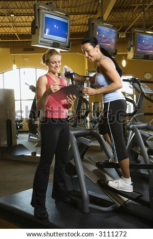 Prime adult Caucasian female on elliptical machine at gym with trainer. - stock photo
