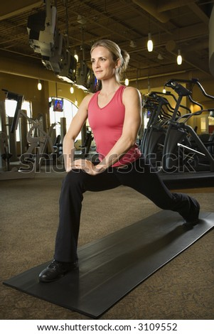 Prime adult Caucasian female stretching on mat in gym. - stock photo