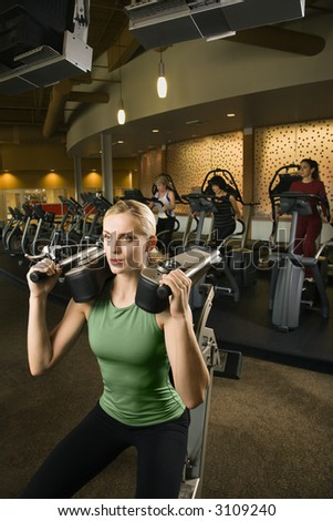 Prime adult Caucasian female using exercise equipment at gym.