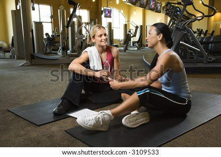 Prime adult Caucasian female with personal trainer at gym. - stock photo