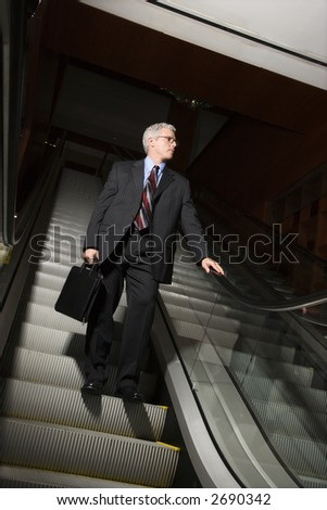 Prime adult Caucasian man in suit holding briefcase standing on down escalator holding rail.