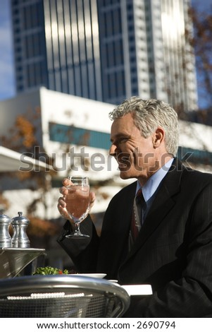 Prime adult Caucasian man in suit sitting outside drinking water at patio table in urban setting.