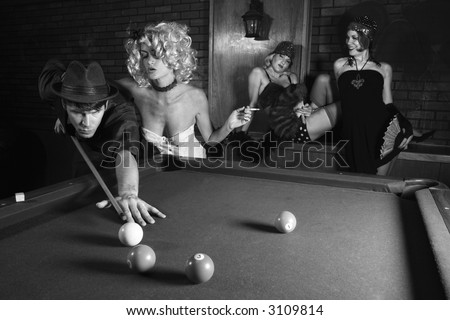 Prime adult Caucasian retro male shooting pool with three Caucasian prime adult retro females watching. - stock photo
